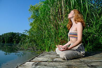 Junge Frau macht Yoga am See - p427m2209793 von Ralf Mohr