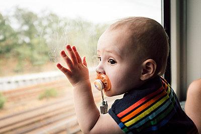 Baby boy gazing out train window - p795m2160956 by JanJasperKlein