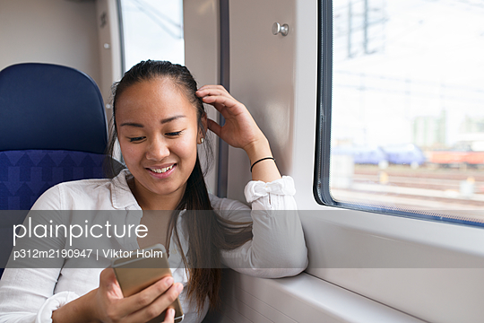 Smiling woman using cell phone in train - p312m2190947 by Viktor Holm