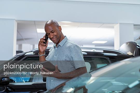 UK, Man talking on smart phone and looking at digital tablet in parking garage - p924m2300782 by Monty Rakusen