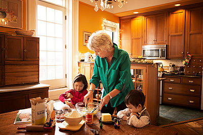 Grandmother with kids preparing cookies at home during Christmas - p1166m1038156f by Cavan Images
