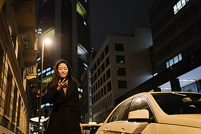 Young woman using smartphone in the city at night, Frankfurt, Germany - p300m2188108 by Hernandez and Sorokina