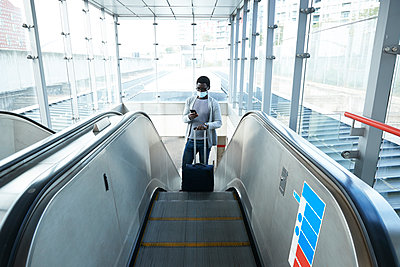 Businessman with luggage using smart phone while standing on escalator at railroad station during COVID-19 - p300m2241552 by Pete Muller
