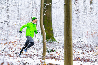 Young male athlete running in forest during winter - p300m2257282 by Stefan Schurr