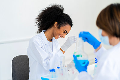Smiling female researcher working with coworker while experimenting in laboratory - p300m2265560 by Giorgio Fochesato