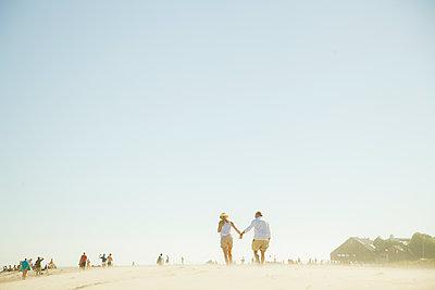 USA, California, Malibu, Couple holding hands on beach - p352m1186863 by Daniel Sahlberg