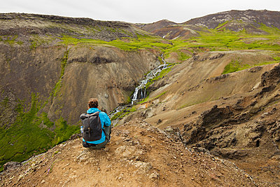 Iceland, Sudurland, Hveragerdi, Reykjadalur, Tourist looking at stream and waterfalls in rocky valley - p352m1349345 by Gustaf Emanuelsson