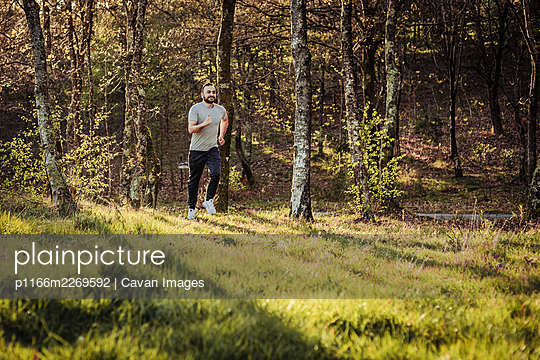 Man in cap and dark tracksuit running through the forest - p1166m2269592 by Cavan Images