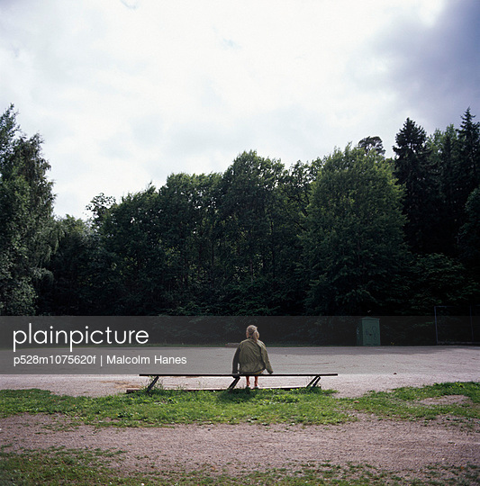 A lonely girl sitting on a bench.
