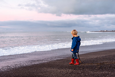 Curly haired preschooler looking at the sea - p1166m2137178 by Cavan Images