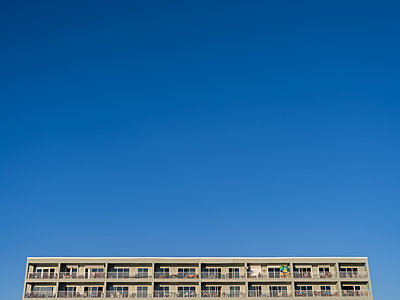 Apartment building against blue sky - p1335m1586375 by Daniel Cullen