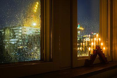 Weihnachtlicher Kerzenleuchter am Fenster in regnerischer Nacht - p1418m1572143 von Jan Håkan Dahlström