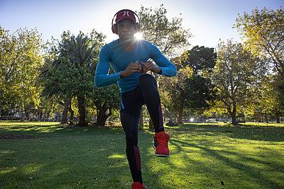Dark-skinned man in sportswear warms up - p1640m2260996 by Holly & John