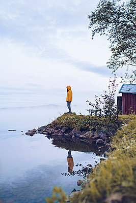 Sweden, Lapland, man wearing  windbreaker standing at water's edge looking at distance - p300m2059552 by CSSHOT