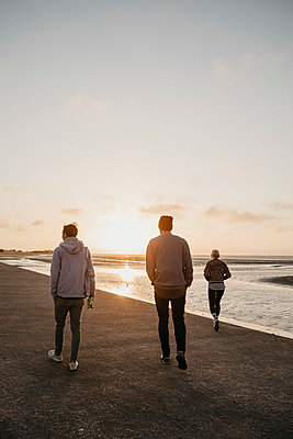 Namibia, Walvis Bay, back view of three friends walking on the beach at sunset - p300m2081056 von letizia haessig photography