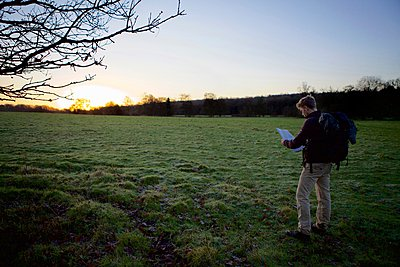 Male hiker reading map in field at sunset - p429m1021746f by Dale Reubin