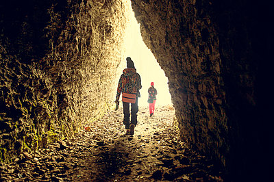 Caucasian hikers walking in rocky cave - p555m1412842 by Aleksander Rubtsov