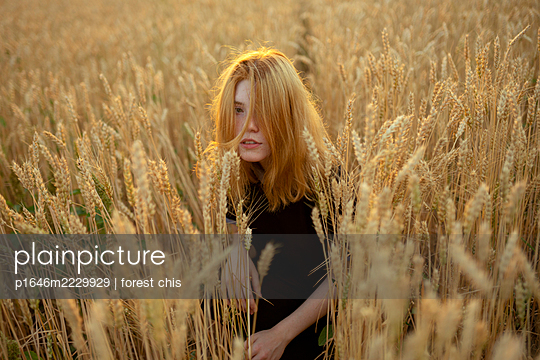 Young woman hiding in a cornfield - p1646m2229929 by Slava Chistyakov