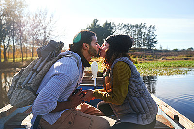 Affectionate young couple kissing in rowboat on sunny autumn lake - p1023m2212943 by Trevor Adeline