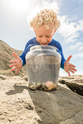 Happy child watching hermit crabs in a bucket - p1166m2138190 by Cavan Images