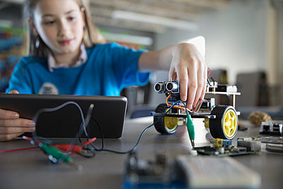 Pre-adolescent girl programming robotics at digital tablet in classroom - p1192m1231099 by Hero Images