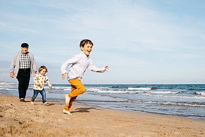 Grandfather strolling with his grandchildren on the beach - p300m2103275 von Josep Rovirosa