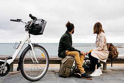 Couple sitting on a bench at beach promenade next to e-bike looking at the sea - p300m2104067 by Josep Rovirosa