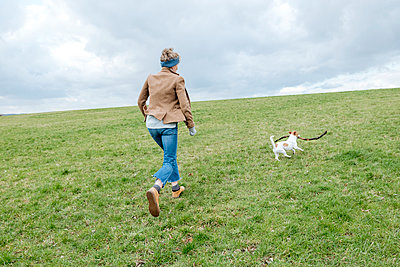 Back view of mature woman playing with her dog on a meadow - p300m2170865 by Katharina und Ekaterina