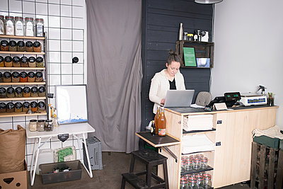 Woman using laptop in shop - p312m2138946 by Viktor Holm