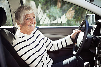 Cheerful senior woman sitting on driver seat in car - p4269330f by Maskot