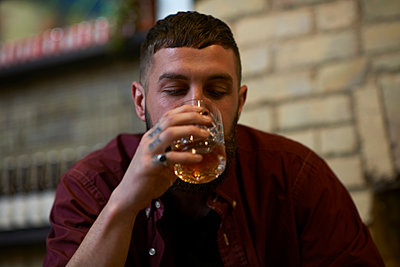 Young man with tattooed fingers drinking tumbler of spirit in public house - p429m1417543 by Peter Muller