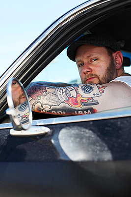 Portrait with tattoed arm in a car - p906m709969 by Wassily Zittel