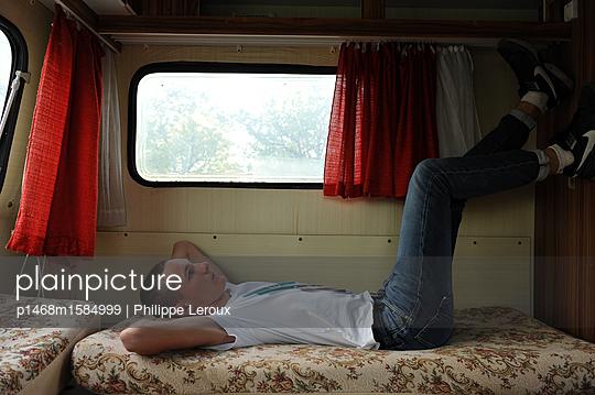 Jugendlicher ruht sich aus in seinem Wohnwagen - p1468m1584999 von Philippe Leroux
