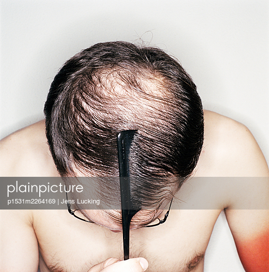 Man with receding hairline, combing hair, close-up - p1531m2264169 by Jens Lucking