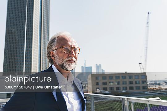 Serious mature businessman in the city looking around - p300m1587047 von Uwe Umstätter