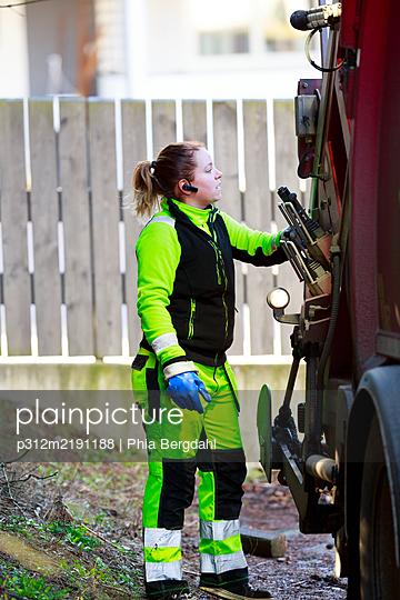 Woman operating garbage truck - p312m2191188 by Phia Bergdahl