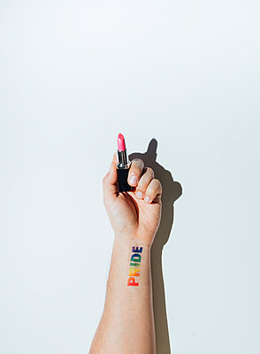 Gay guy's hand with a tattoo that says pride and nail polish. - p1166m2191811 by Cavan Images
