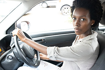 Young african woman at the steering wheel in a car - p1640m2260074 by Holly & John