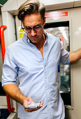 UK, London, businessman in underground train looking at cell phone - p300m2062080 von Marco Govel