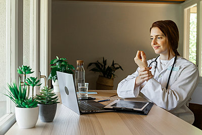 Young female doctor holding wrist while explaining during online consultation at home office - p300m2224896 by VITTA GALLERY