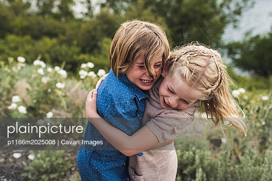 Happy sisters embracing while standing against plants in forest - p1166m2025008 by Cavan Images