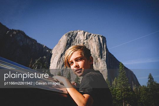 Blonde Boy Hangs from Car window with El Cap in the Background - p1166m2261942 by Cavan Images