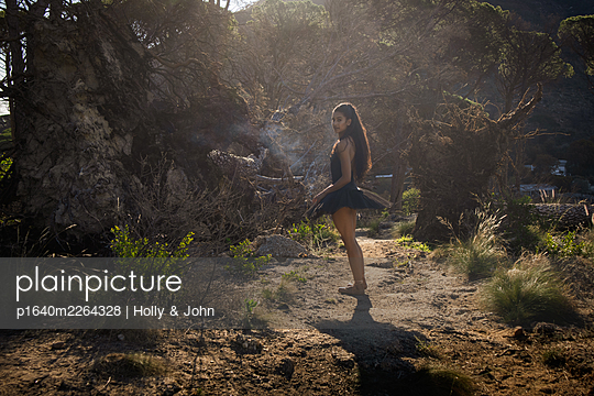 Woman in ballet skirt goes for a walk in the countryside - p1640m2264328 by Holly & John