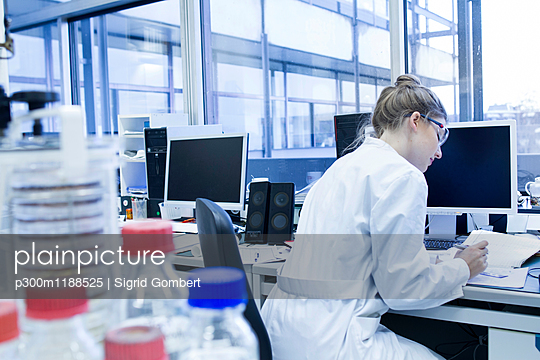 Biologist working in laboratory at desk - p300m1188525 by Sigrid Gombert