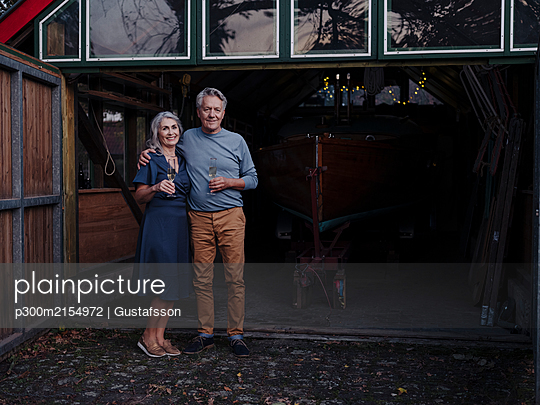 Senior couple standing in front of boathouse with glass of champagne - p300m2154972 by Gustafsson