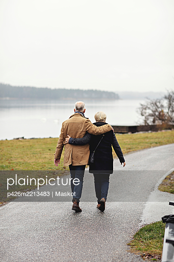 Rear view of senior couple with arm around walking on footpath during winter - p426m2213483 by Maskot