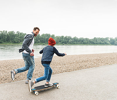 Happy father running next to son on skateboard at the riverside - p300m2004357 von Uwe Umstätter