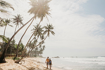 Rear view of romantic couple walking on sea shore at beach against sky, Sri Lanka - p300m2140870 by letizia haessig photography