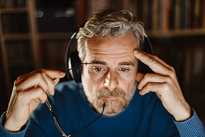 Portrait of pensive mature man with headphones in front of computer - p300m2180489 by 27exp