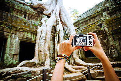 Cambodia, Angkor Wat, Woman takes pictures of the famous tree in Ta Prohm Temple - p300m873971f by Martin Benik